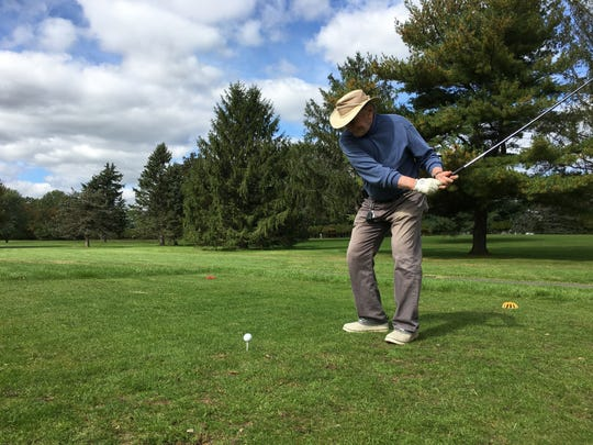 Dr. Barry Grabelle playing golf.