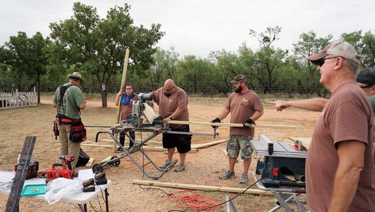 Adam Quintanilla, center, saws woods at a worksite.