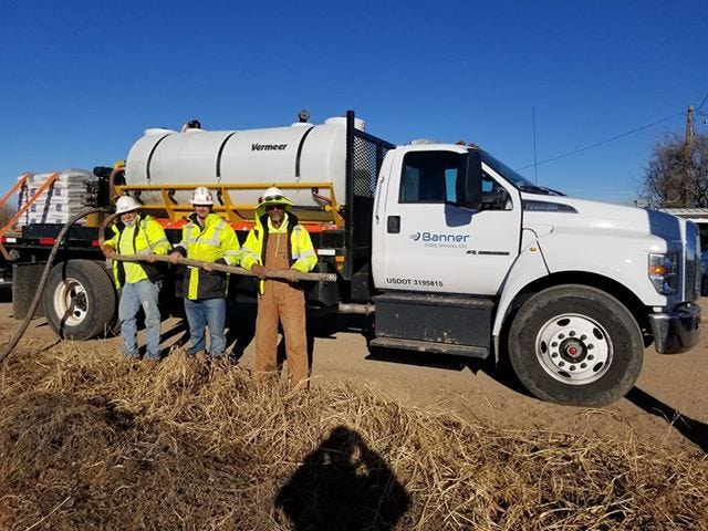 David Rodriguez, left, along with Blayne Keplinger and Bill Hice hold the hose of their water tanker truck after using its contents to extinguish a car fire along County Road 605 near Hawley on Dec. 20. Their quick reaction after finding the family flagging them down for help, prevented the fire from spreading to the field behind it.