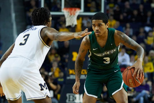 Binghamton Bearcats guard Sam Sessoms (right) controls the ball against Michigan Wolverines guard Zavier Simpson (left) in the second half at Crisler Center.