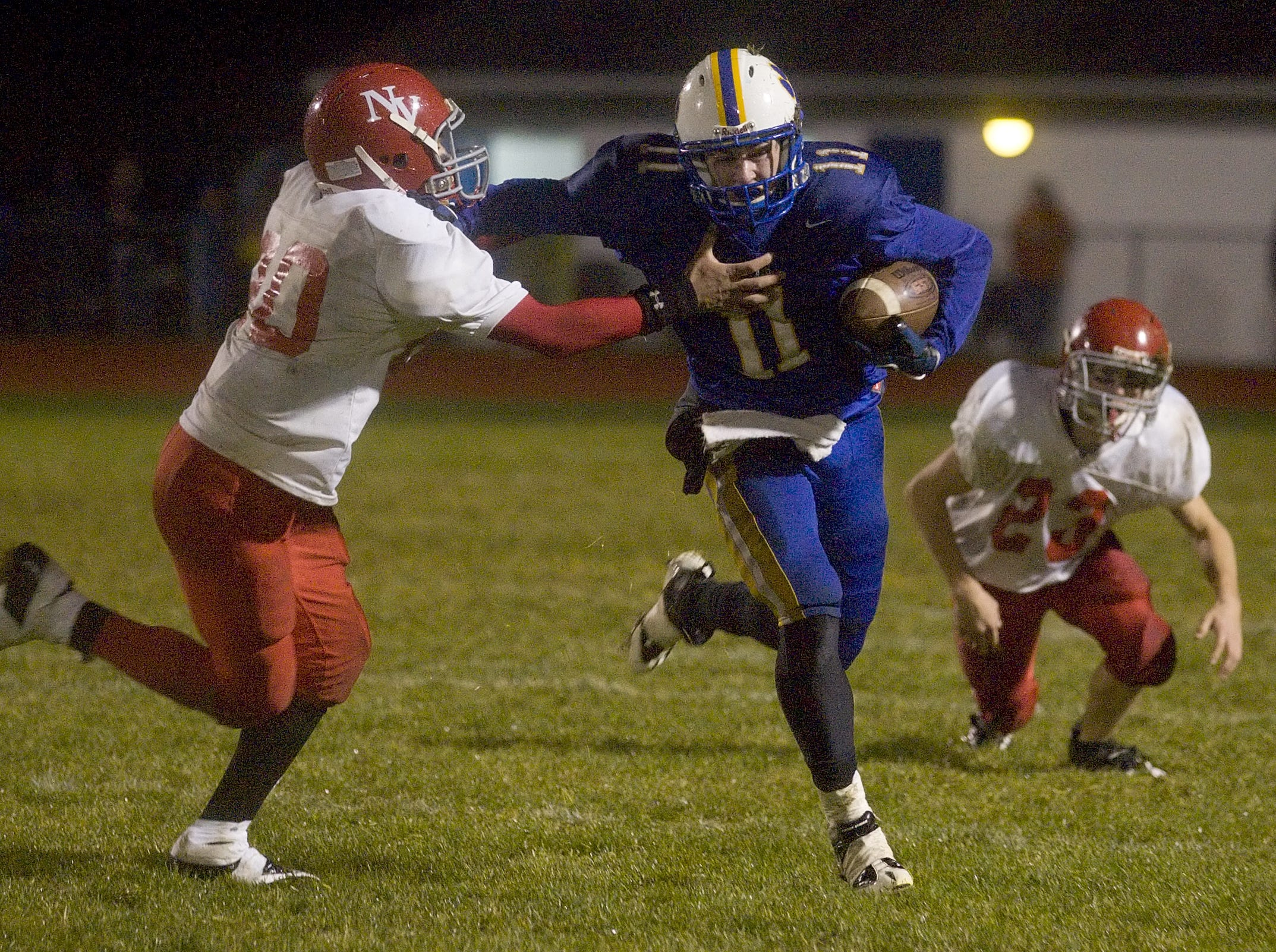 From 2009: Newark Valley's Christian Tapia left attempts to tackle Lansing's TJ Cretney center with Newark Valley's John Stagg trailing on the play during the second quarter of the game on Friday at Lansing.