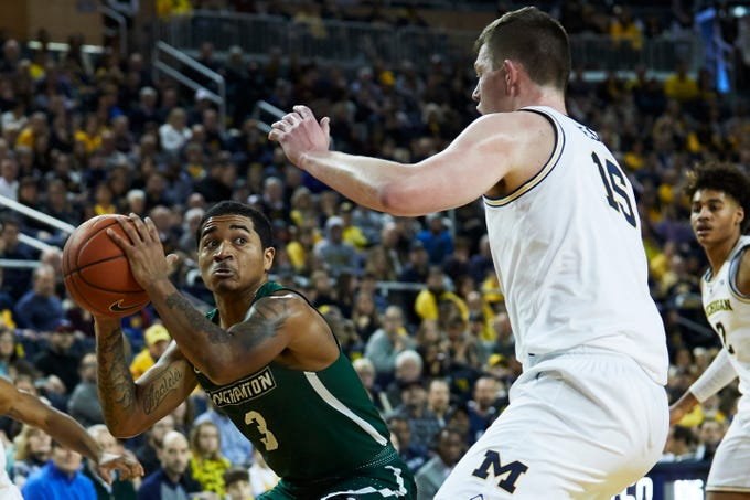 Binghamton Bearcats guard Sam Sessoms controls the ball against Michigan Wolverines center Jon Teske in the second half Sunday, Dec. 30. No. 2 Michigan pulled away for a 74-52 victory over Binghamton.