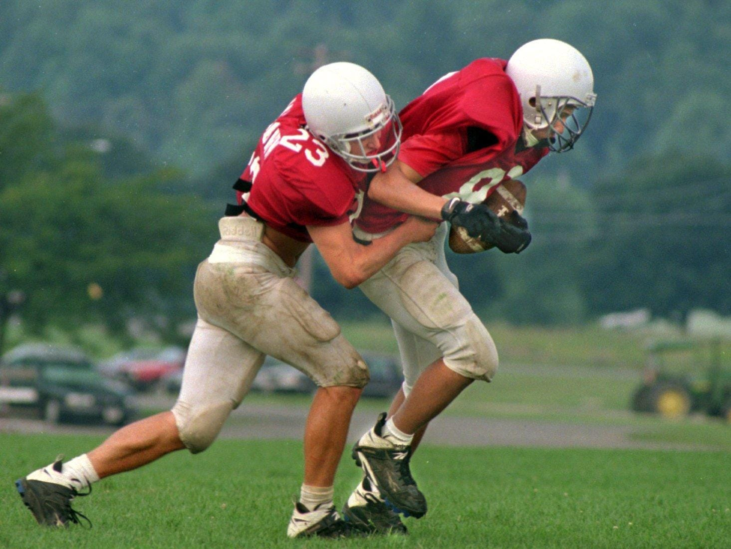 From 1996: HS Tab Newark Valley's Taylor Vaughn (#23) pulls down John Cornell during defensive drills at practice.