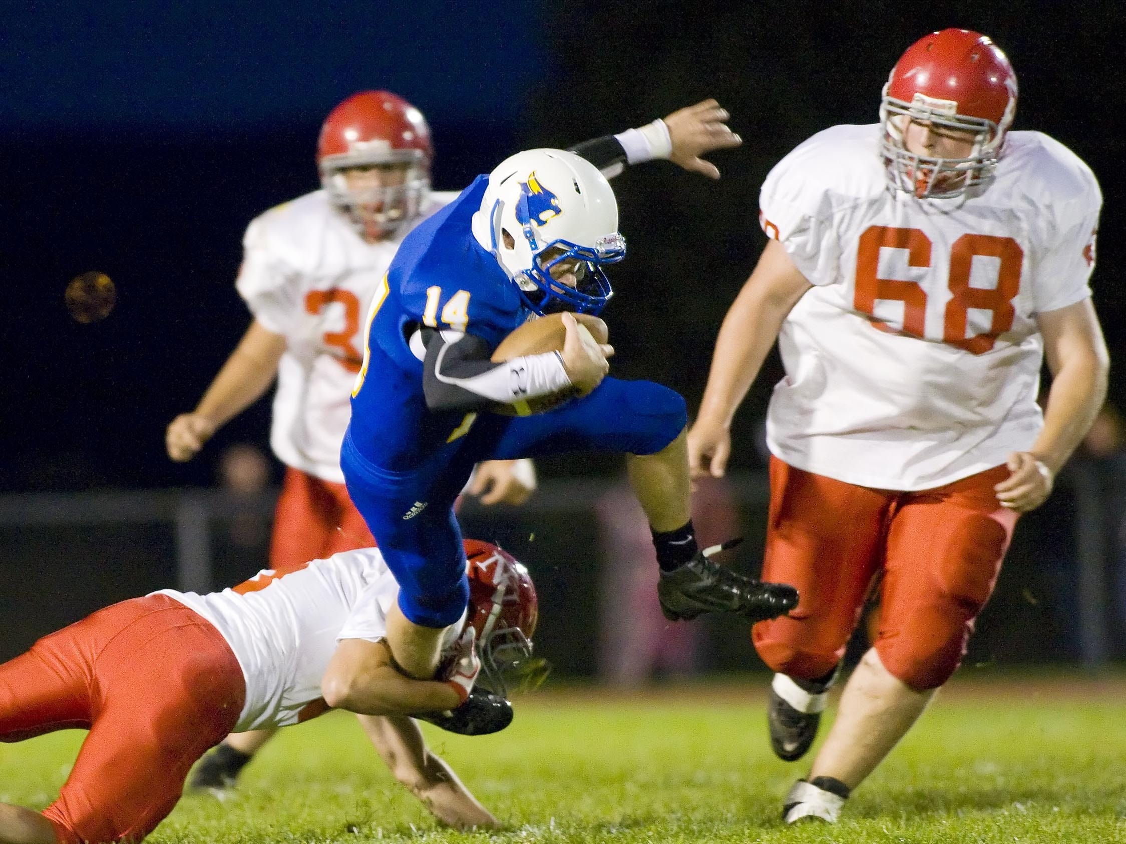 From 2011: Newark Valley's Nick Whitmarsh hangs on to bring down Lansing's Corey Dake as Newark Valley's Cody French right comes to help out during the first half of their game Friday evening in Lansing.