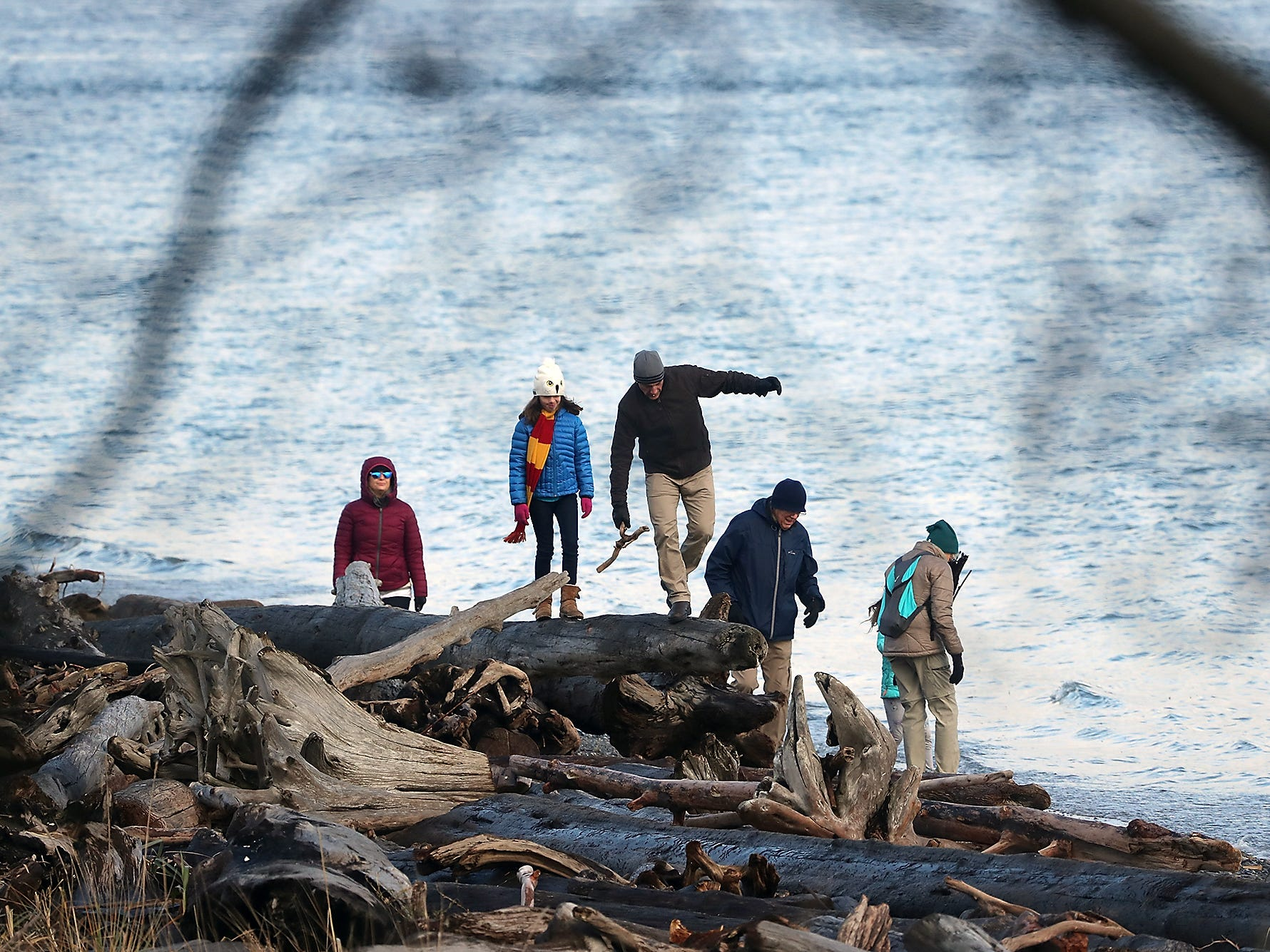 Beach walkers balance on the driftwood logs as they make their way down the shore at Point No Point in Hansville on Sunday, December 30, 2018.