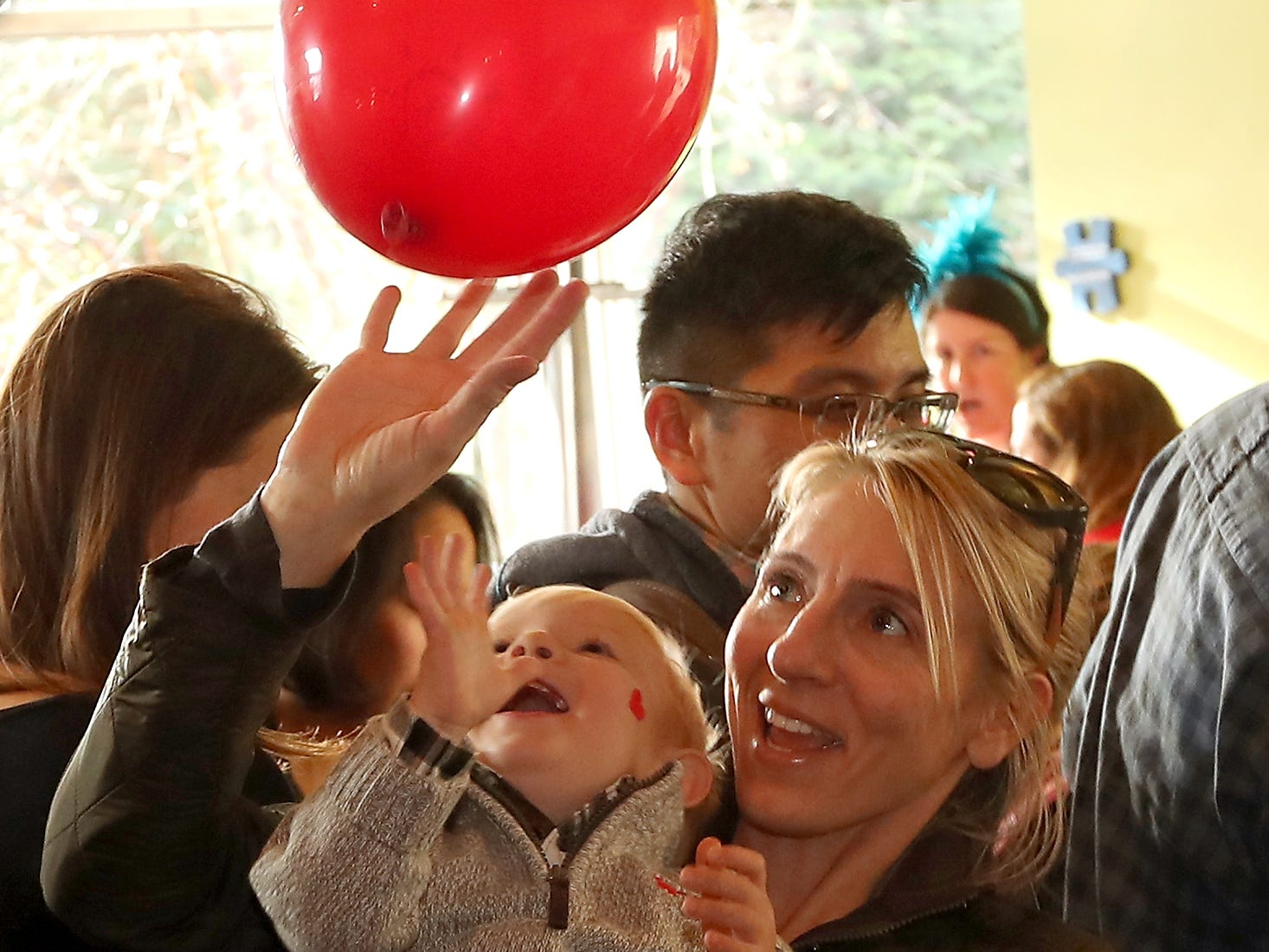Ashley Hankins taps a balloon into the air as 20-month-old son Roman Fryer laughs while they ring in 2019 with the Noon Years Eve party at Bainbridge Island's KiDiMu (Kids Discovery Museum) on Monday, December 31, 2018.
