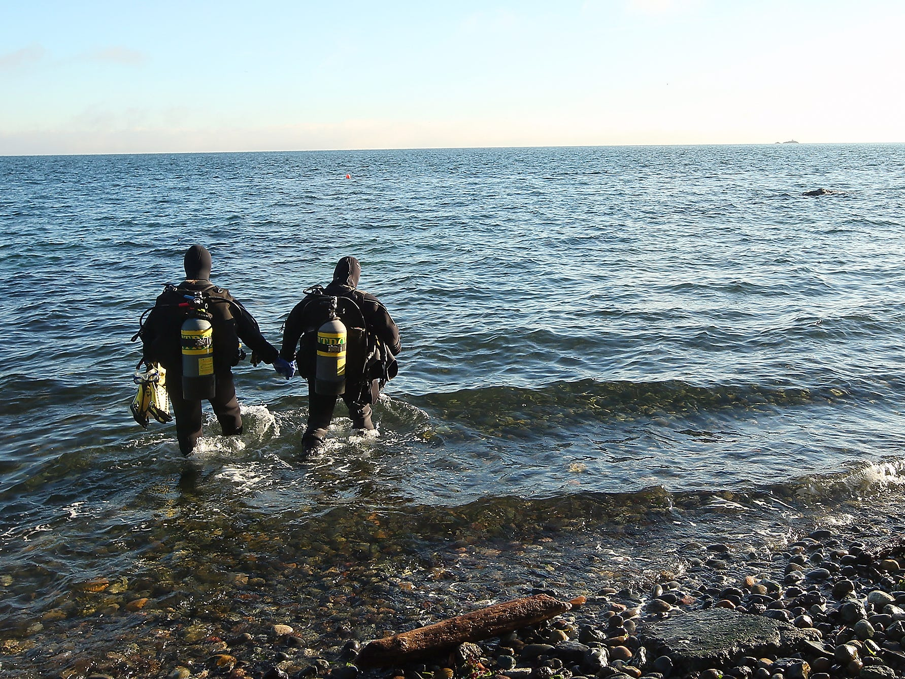 Scuba divers Jackie Wood and Rick Hatten hold hands as they enter the water at Bainbridge Island's Rockaway Beach on Monday, December 31, 2018.