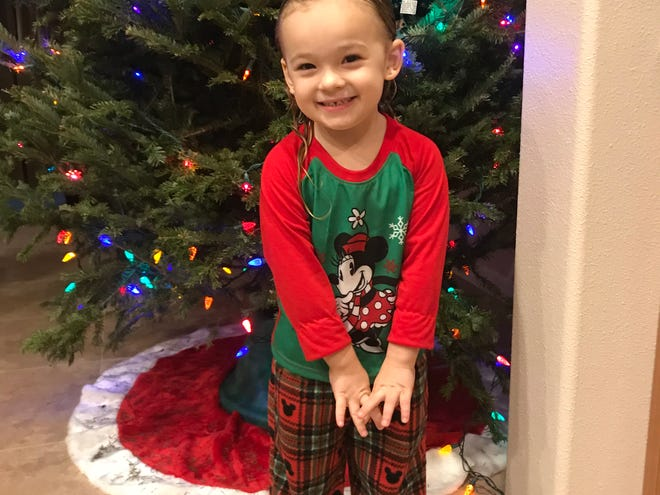 Isabella poses in front of her Christmas tree after showering and putting on her new pajamas. Some nights are easier that others when it comes to getting her cleaned up.