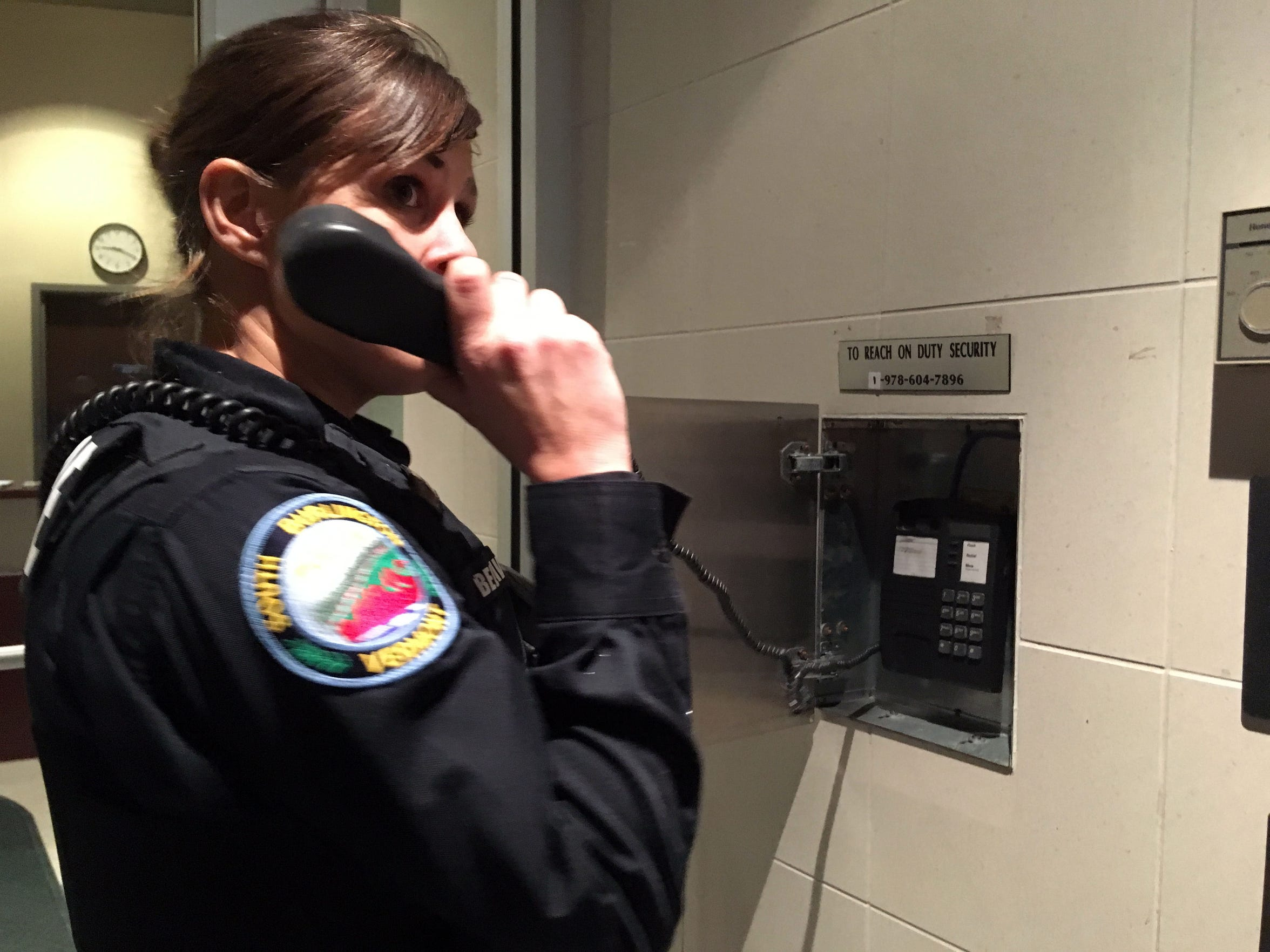 South Burlington Police Officer Sarah Bellavance attempts to reach a security officer through a phone outside an IDX Drive building on Dec. 6, 2018.
