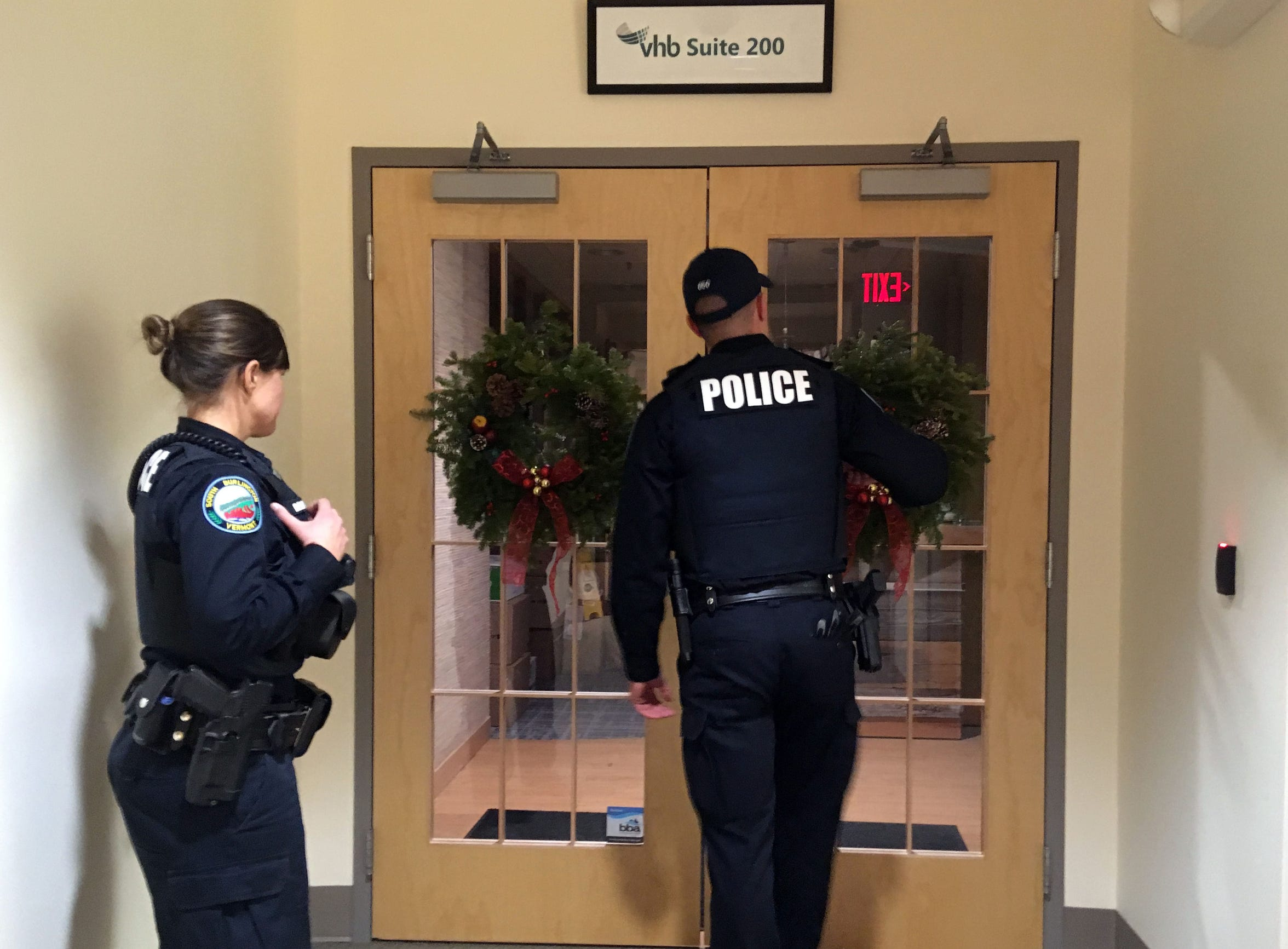 South Burlington Police Officer Sarah Bellavance, left, and another officer check the door of an IDX Drive business on Dec. 6, 2018, after responding to a report of an alarm sounding inside.
