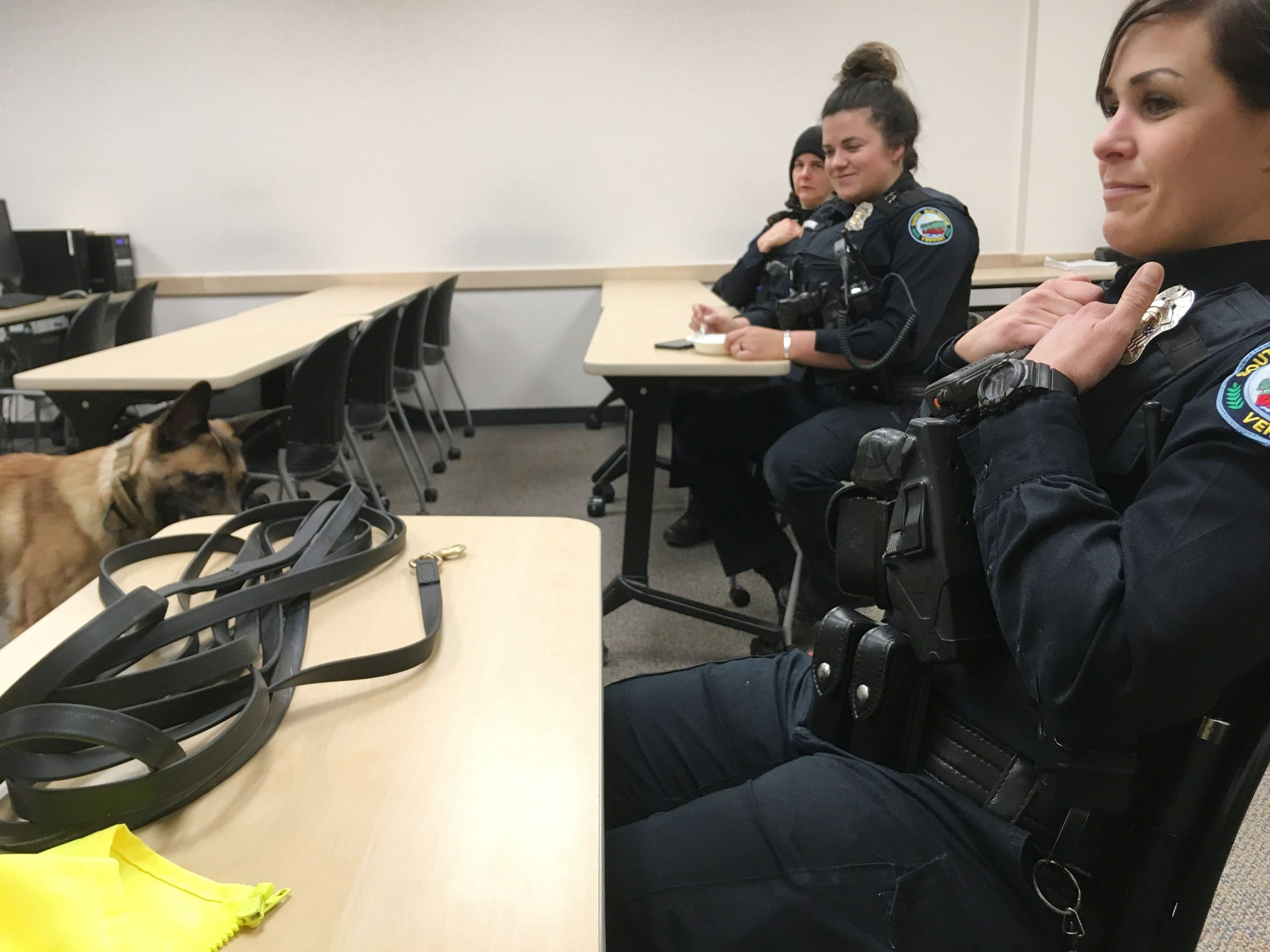 From right, South Burlington Police officers Sarah Bellavance and Kelsey Monroe and Cpl. Karen Chevalier listen during roll call on Dec. 6, 2018. K9 Rush plays in the background.
