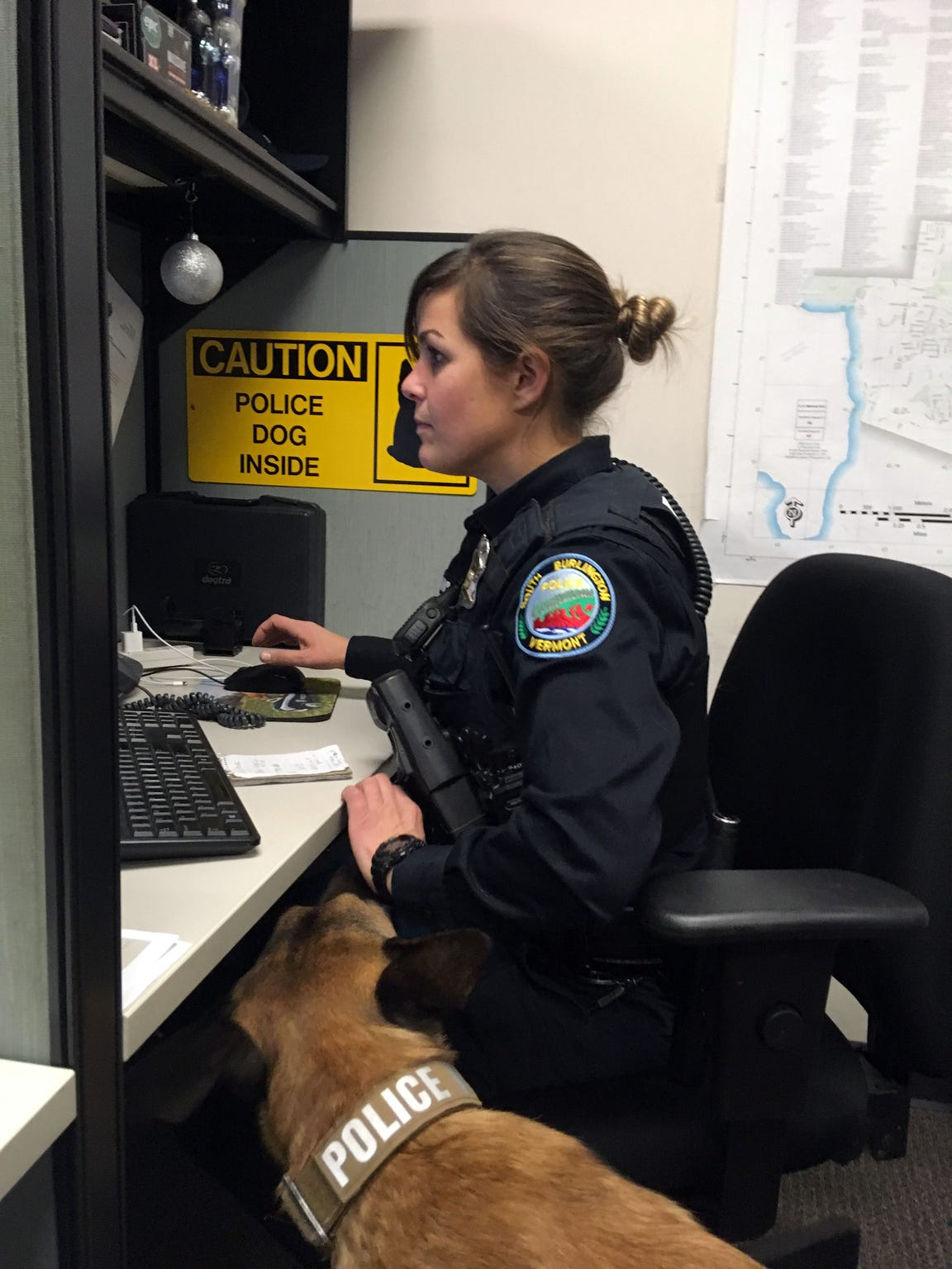 South Burlington Police Officer Sarah Bellavance attempts to complete paperwork on her computer while K9 Rush tries to goad her into playing on Dec. 6, 2018.