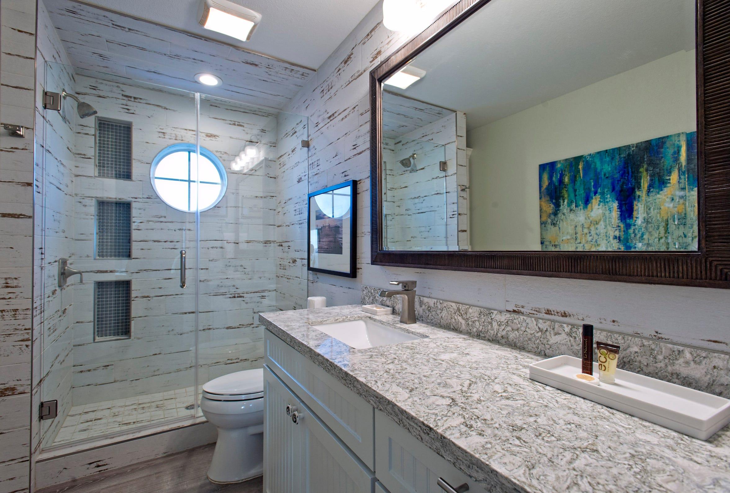 The unique ceramic shiplap planked walk in shower compliments the quartz countertops in the master bath