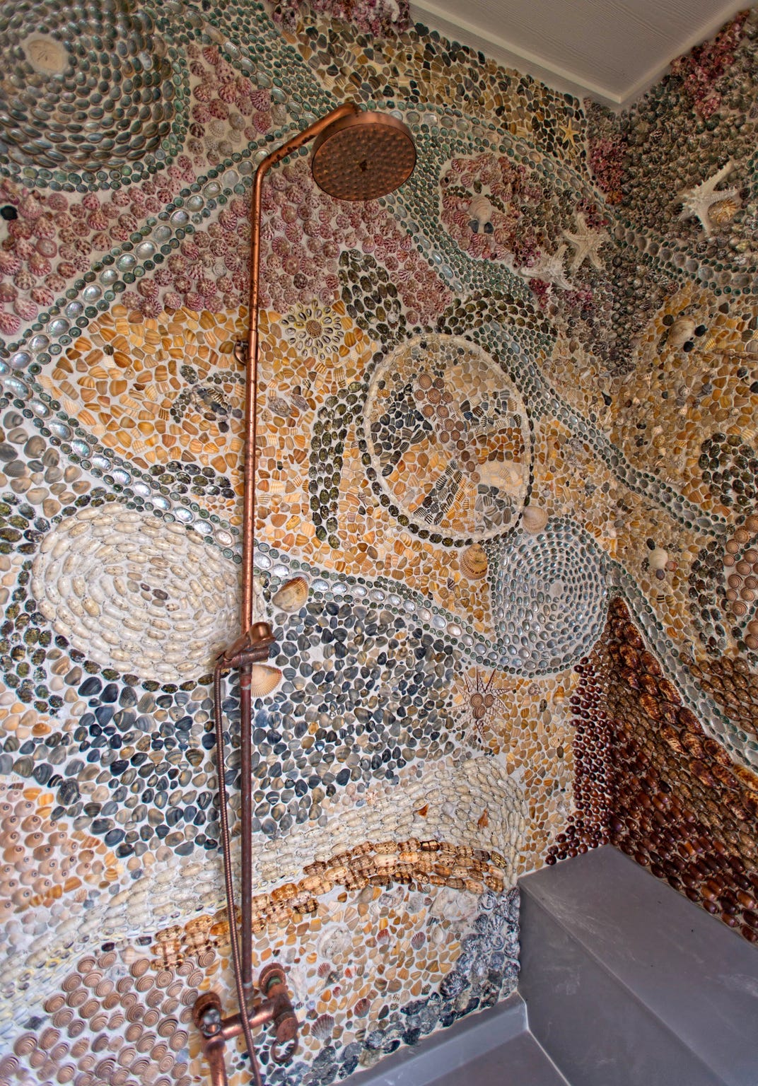 The outdoor shower is a work of art with an invalid mosaic of shell and rock with a turtle theme.