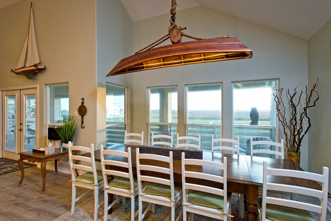 The open dining area features a unique custom made canoe light fixture.
