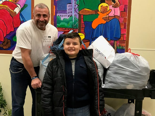 Jim Catrambone, left, and Tavit Murray  wheel bag of donated jeans into a Camden homeless shelter administered by the Joseph Fund of Camden. The jeans were donated to Denim American Bistro in Cherry Hill by customers. Tavit's family owns the restaurant.