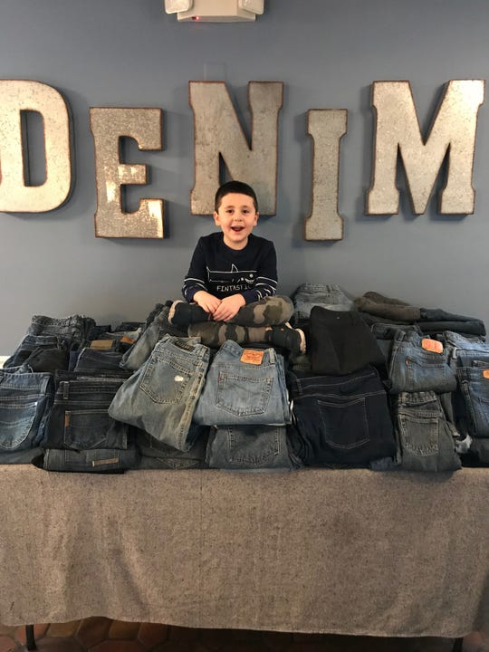 Spencer Murray, 5, sits atop a giant stack of jeans donated to Denim American Bistro. Tavit went with his parents to a shelter run by the Joseph Fund of Camden to deliver the jeans, which were donated to the Cherry Hill restaurant by its guests.