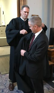 Ross County Juvenile and Probate Judge Jeff Benson helps newly sworn in Ross County Common Pleas Judge Matt Schmidt put on a judge's robe provided to Schmidt by the Ross County Bar Association.