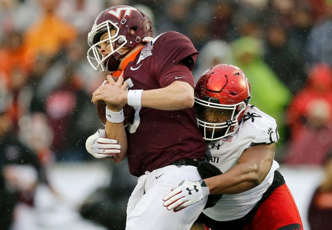 Virginia Tech Hokies quarterback Ryan Willis (5) is wrapped up by Cincinnati Bearcats defensive tackle Cortez Broughton (96) in the first quarter of the Military Bowl at Navy–Marine Corps Memorial Stadium in Annapolis, Md., on Monday, Dec. 31, 2018. The game was tied at 14 after the first half.