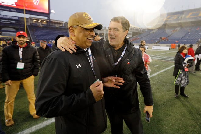 University of Cincinnati President Neville G. Pinto and Athletic Director Mike Bohn hug after the fourth quarter of the Military Bowl at Navy–Marine Corps Memorial Stadium in Annapolis, Md., on Monday, Dec. 31, 2018. The Bearcats took home the Military Bowl trophy and complete the team's third-ever 11-win season.