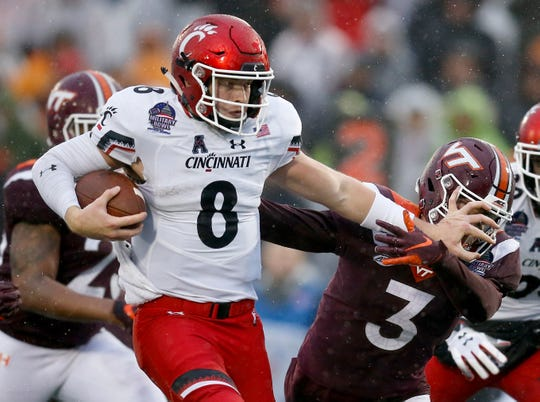 Cincinnati Bearcats quarterback Hayden Moore (8) stiff arms Virginia Tech Hokies defensive back Caleb Farley (3) on his way to a touchdown in the fourth quarter of the Military Bowl at Navy–Marine Corps Memorial Stadium in Annapolis, Md., on Monday, Dec. 31, 2018. The Bearcats took home the Military Bowl trophy and complete the team's third-ever 11-win season.