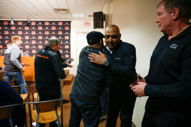 Marvin Lewis leaves his last press conference as Wayne Miller, left, and other media shake his hand on his way out.