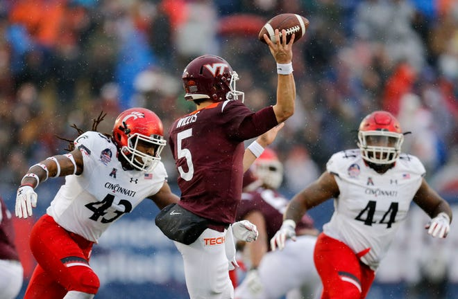 Cincinnati Bearcats defensive end Michael Pitts (43) dives for Virginia Tech Hokies quarterback Ryan Willis (5) as he throws in the second quarter of the Military Bowl at Navy–Marine Corps Memorial Stadium in Annapolis, Md., on Monday, Dec. 31, 2018. The game was tied at 14 after the first half.