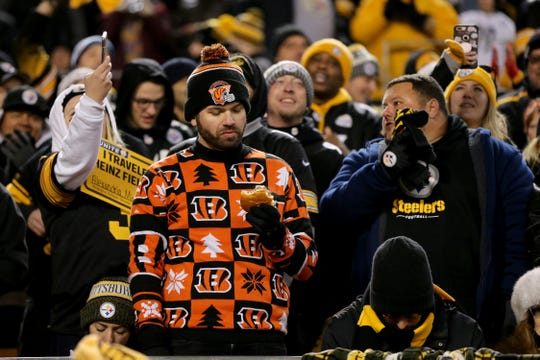 A Cincinnati Bengals fans looks at his hamburger after Pittsburgh Steelers wide receiver JuJu Smith-Schuster (19) scored a touchdown in the third quarter of a Week 17 NFL football game, Sunday, Dec. 30, 2018, at Heinz Field in Pittsburgh. The Cincinnati Bengals lead 10-3 at halftime. The Pittsburgh Steelers won 16-13.