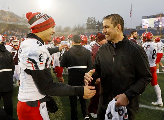 Injured Cincinnati Bearcats starting quarterback Desmond Ridder (9) hugs head coach Luke Fickell after the fourth quarter of the Military Bowl at Navy–Marine Corps Memorial Stadium in Annapolis, Md., on Monday, Dec. 31, 2018. The Bearcats took home the Military Bowl trophy and complete the team's third-ever 11-win season.
