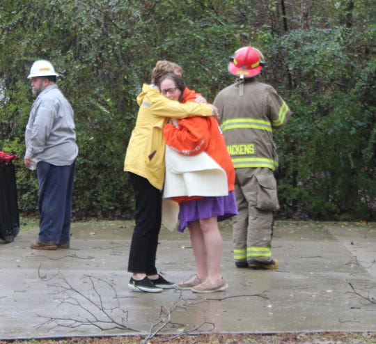 Lindsay Tinsley, whose house was destroyed by a falling tree on Monday, is comforted by a friend.
