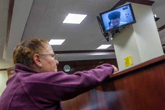 Kristi Ferry watches as Nyoky Steven Bull appears on a monitor for his video arraignment before Judge Geoffrey Nolan at Muskegon County District Court on Friday, Dec. 28, 2018, in Muskegon, Mich. Bull is a suspect in the crossbow homicide of Marcus Olmstead on Wednesday, Dec. 26. Ferry is Marcus' mother.