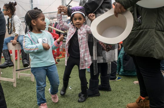 From left, Kylie Styles, 4, of Detroit and Dallas Morrow, 4 of Novi, dance to Top 40 music while waiting to get their faces painted during a family-friendly NYE Kids Countdown on  Monday, Dec. 31, 2018. The event is sponsored by DTE Energy Beacon Park Foundation and programmed by the Downtown Detroit Partnership.