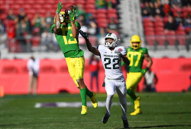 Dillon Mitchell of the Oregon Ducks has the ball bounce off his hands for an incomplete pass against the Michigan State Spartans during the first half.