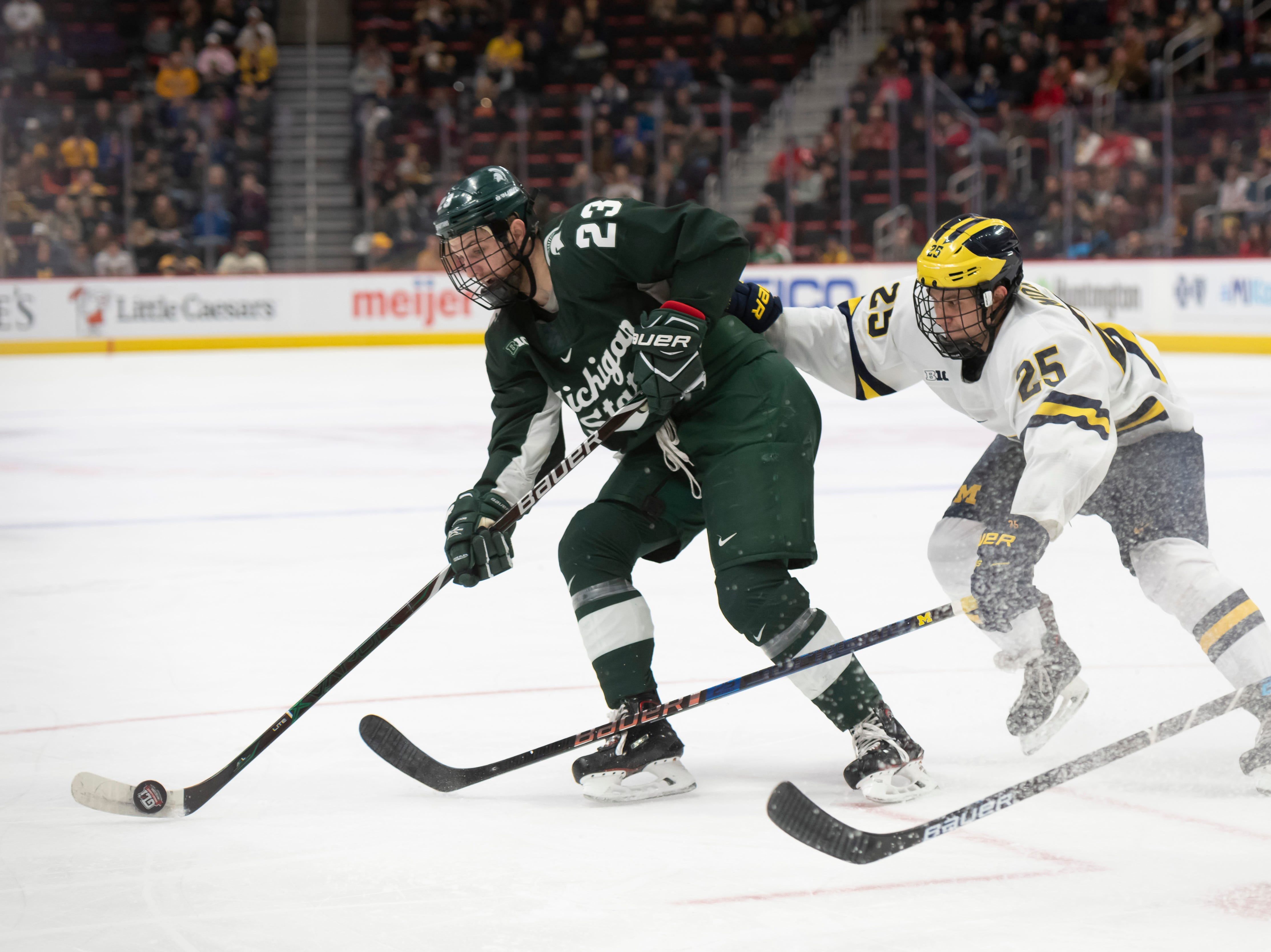 Michigan State forward Cody Milan keeps the puck away from Michigan forward Luke Morgan in the second period.