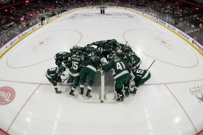 Michigan State rallies around their goalie before the start of the game.            Photos are of Michigan State University vs. the University of Michigan, during the third place game of the Great Lakes Invitational at Little Caesars Arena, in Detroit, Dec. 31, 2018.