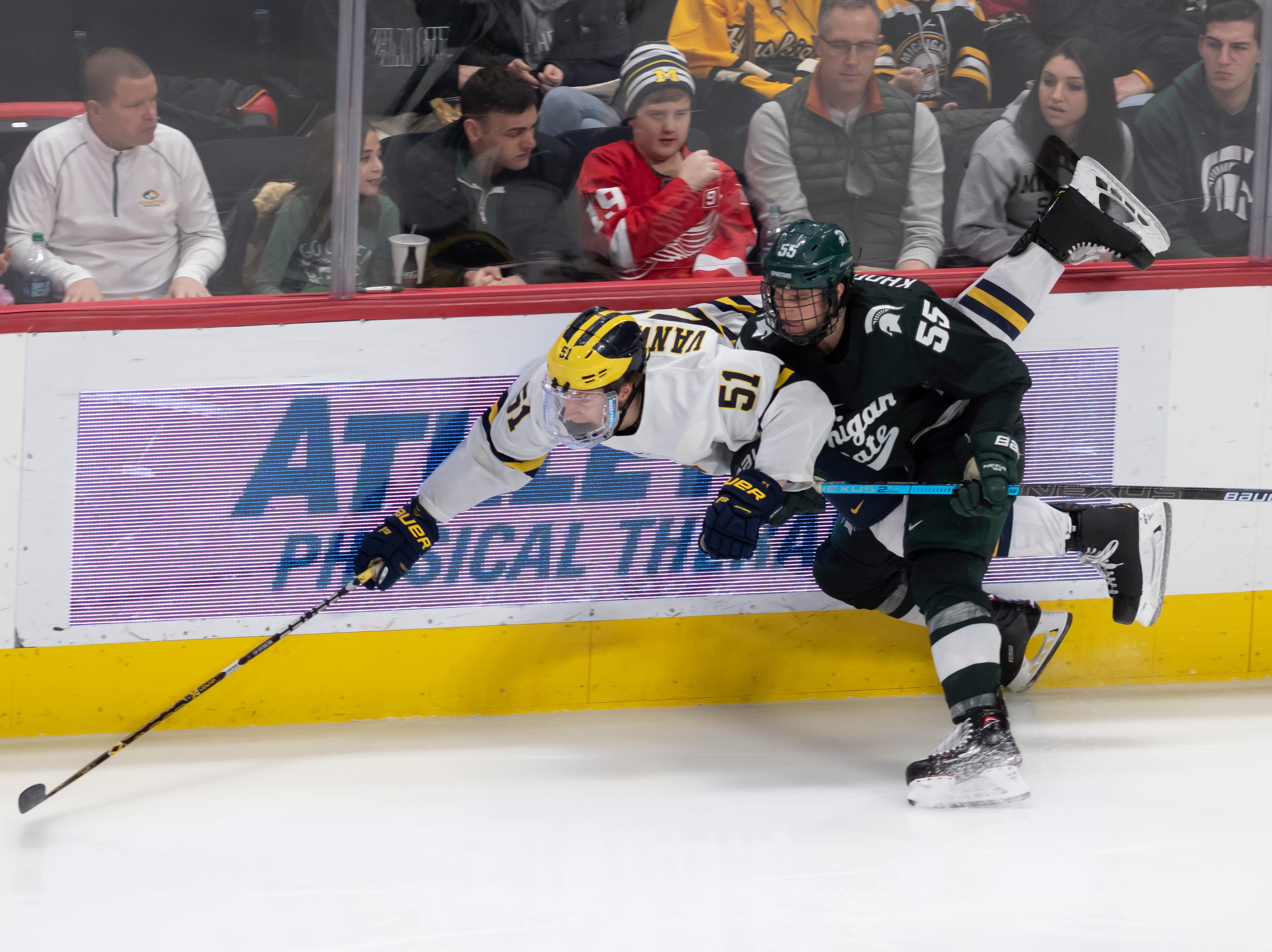 Michigan forward Garrett Van Wyhe gets checked into the boards by Michigan State forward Patrick Khodorenko in the third period.