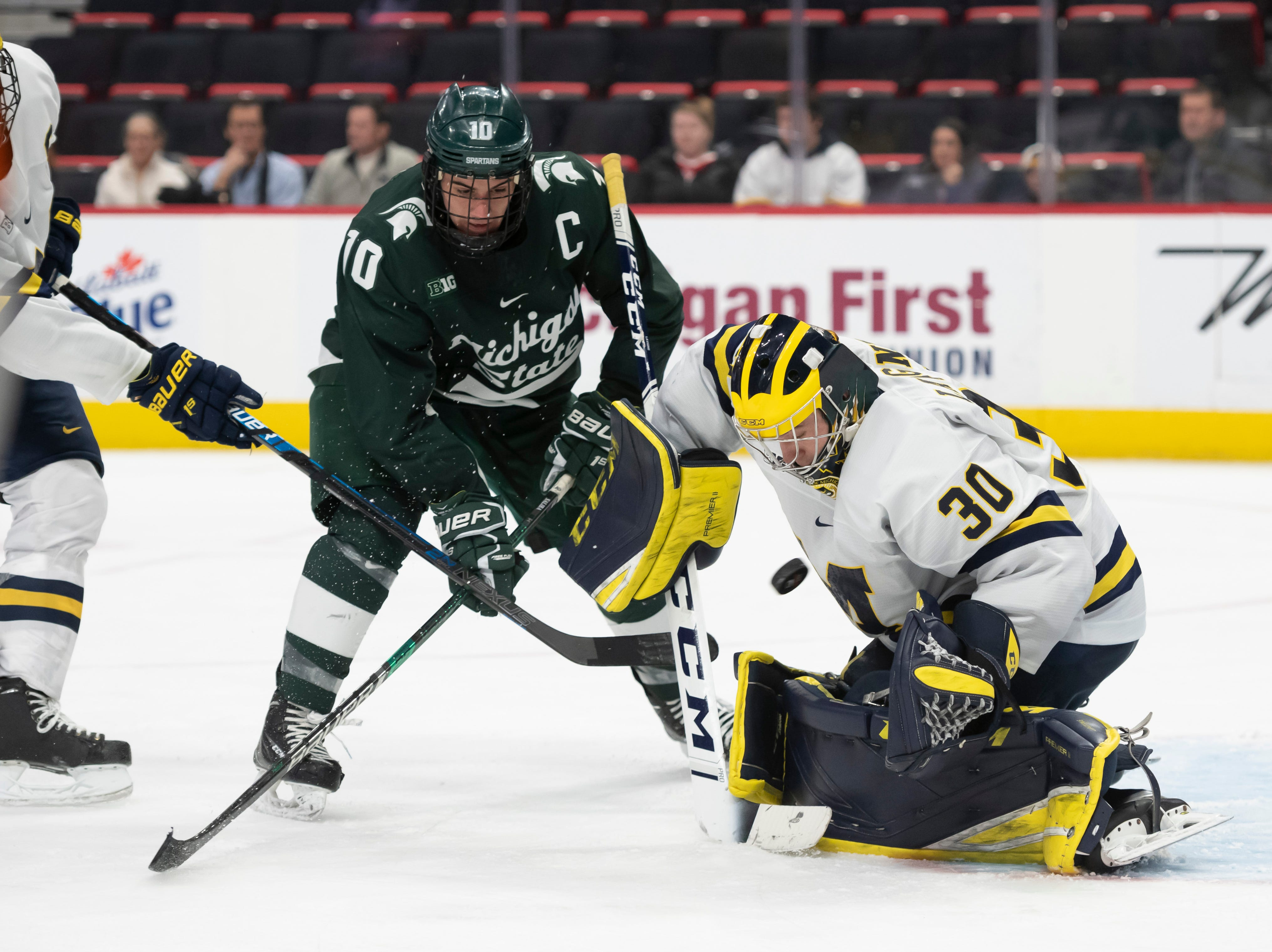 Michigan State forward Sam Saliba tries to get the puck past Michigan goaltender Hayden Lavigne in the second period.