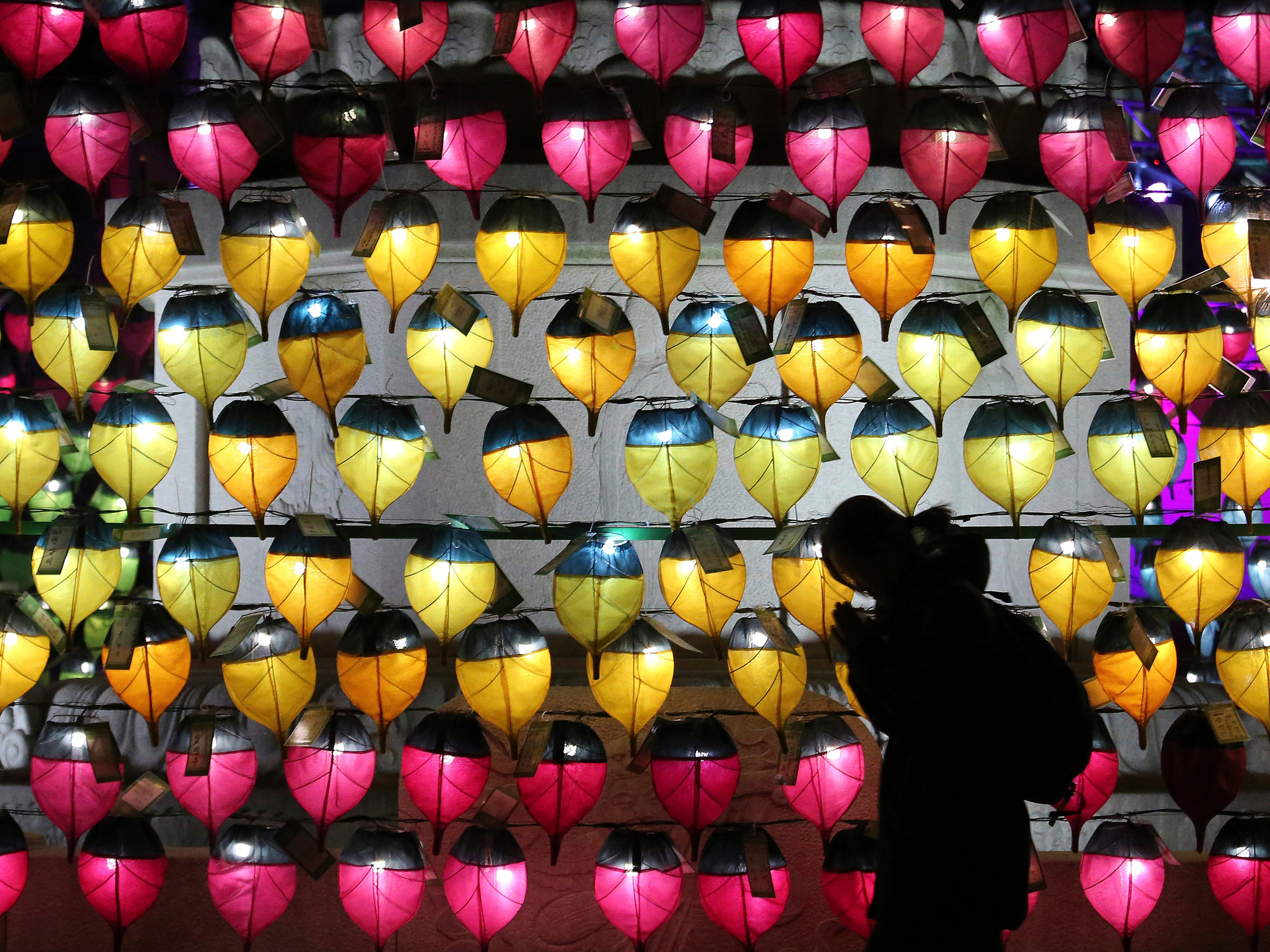 A woman prays in front of a wall of lanterns to celebrate the new year at the Jogyesa Buddhist temple in Seoul, South Korea, Monday, Dec. 31, 2018.