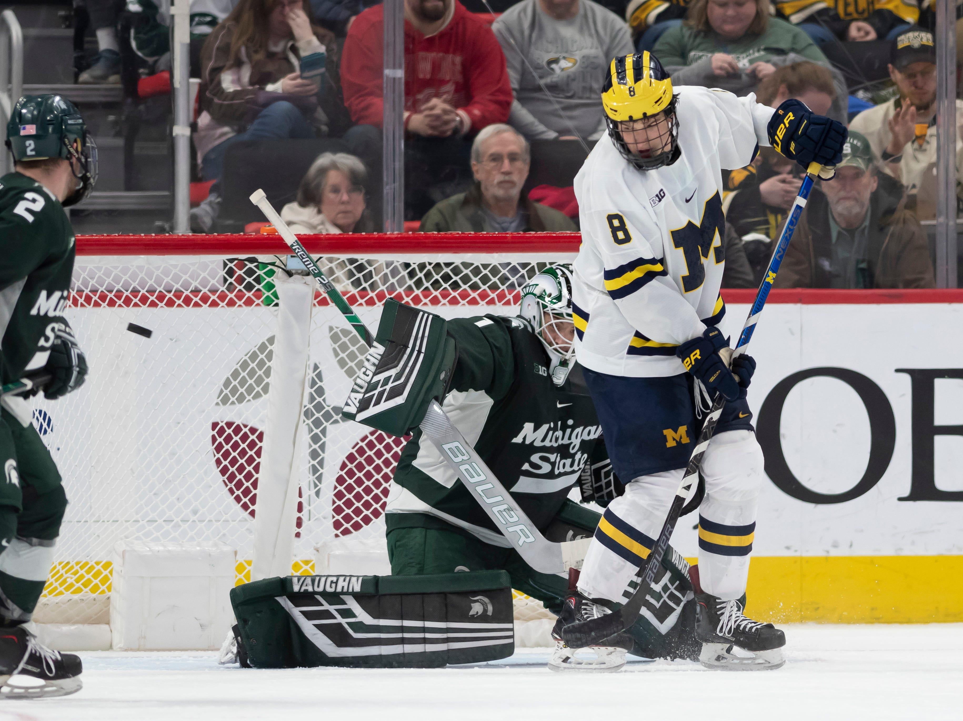 Michigan forward Jack Becker tries to deflect the puck past Michigan State goaltender Drew DeRidder in the second period.