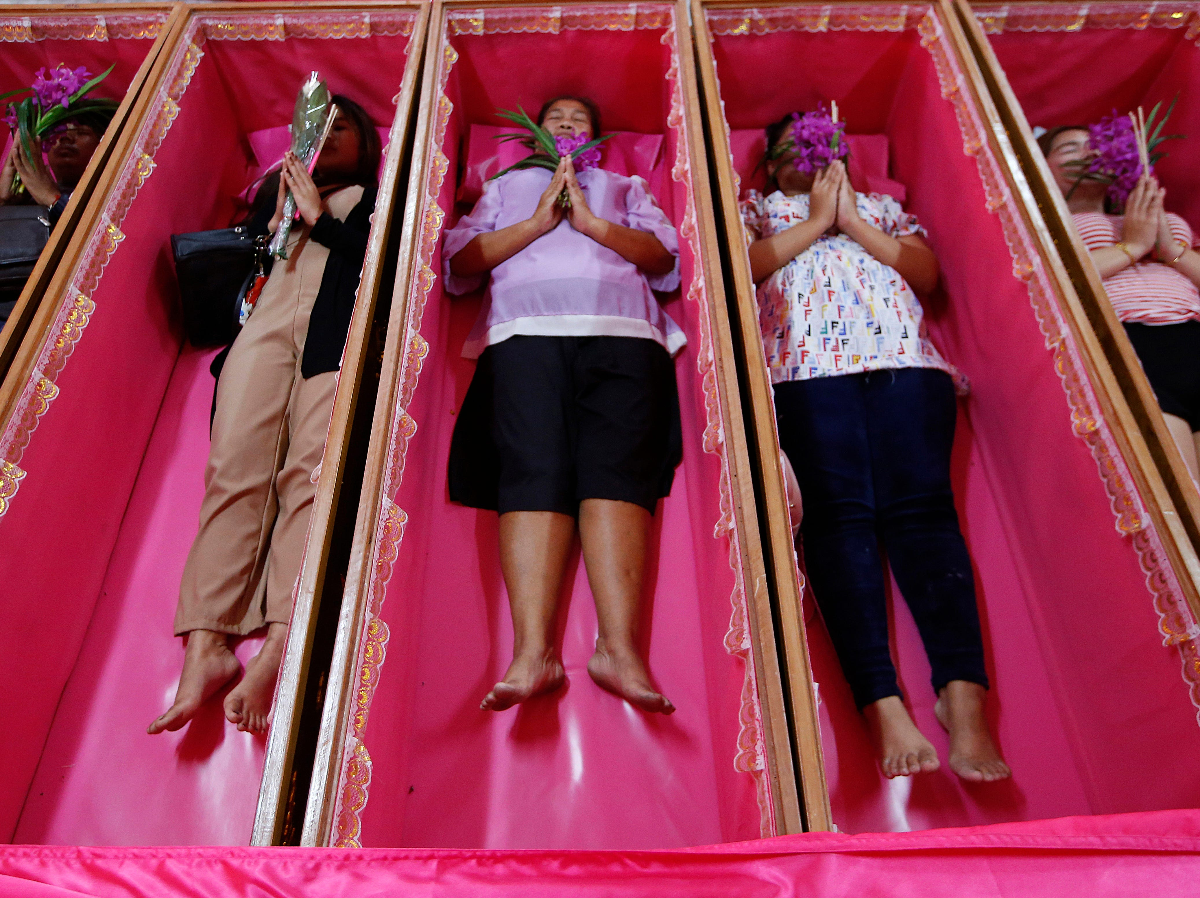 "Worshippers take turns praying in coffins during a ceremony at the Takien temple in suburban Bangkok, Thailand on Dec. 31, 2018. Participants believe the ceremony ""symbolizing death and rebirth"" helps rid themselves of bad luck and are born again for a fresh start in the new year."