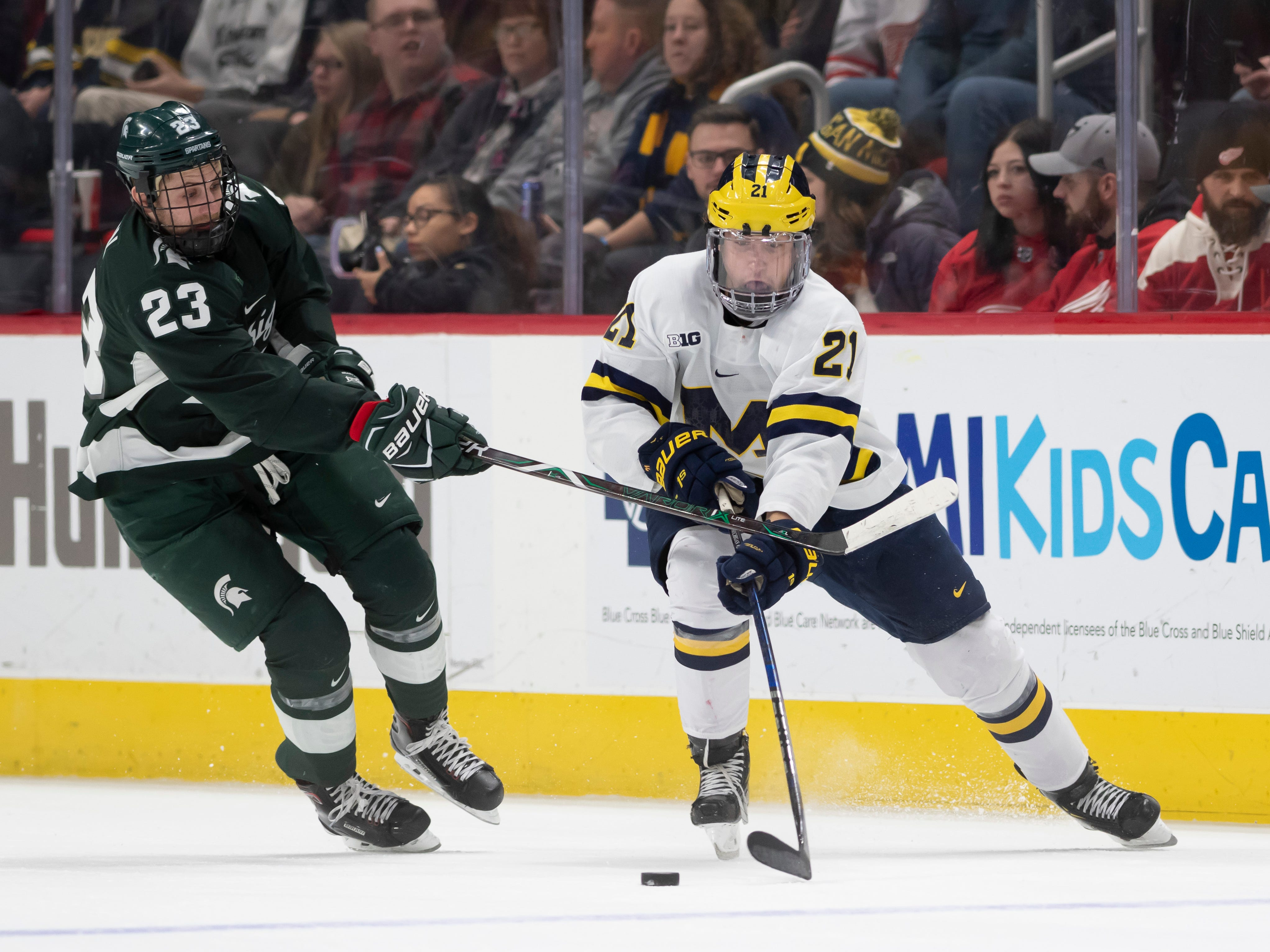 Michigan State forward Cody Milan tries to steal the puck from Michigan forward Michael Pastujov in the first period.