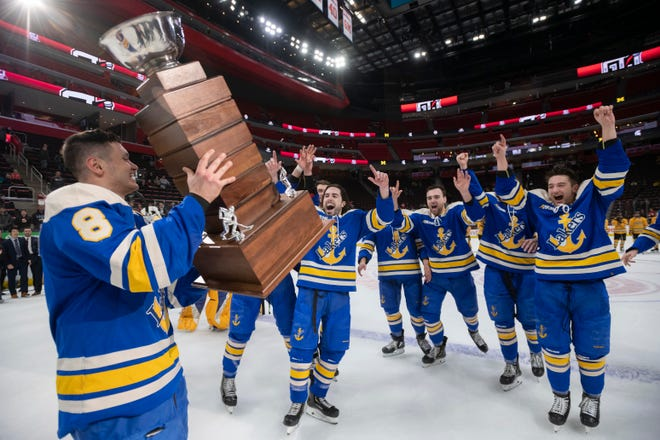 Lake Superior forward Diego Cuglietta, left, presents the MacInnes Cup to his teammates after Lake Superior State defeated Michigan Tech 6-3 to win the championship game of the Great Lakes Invitational.