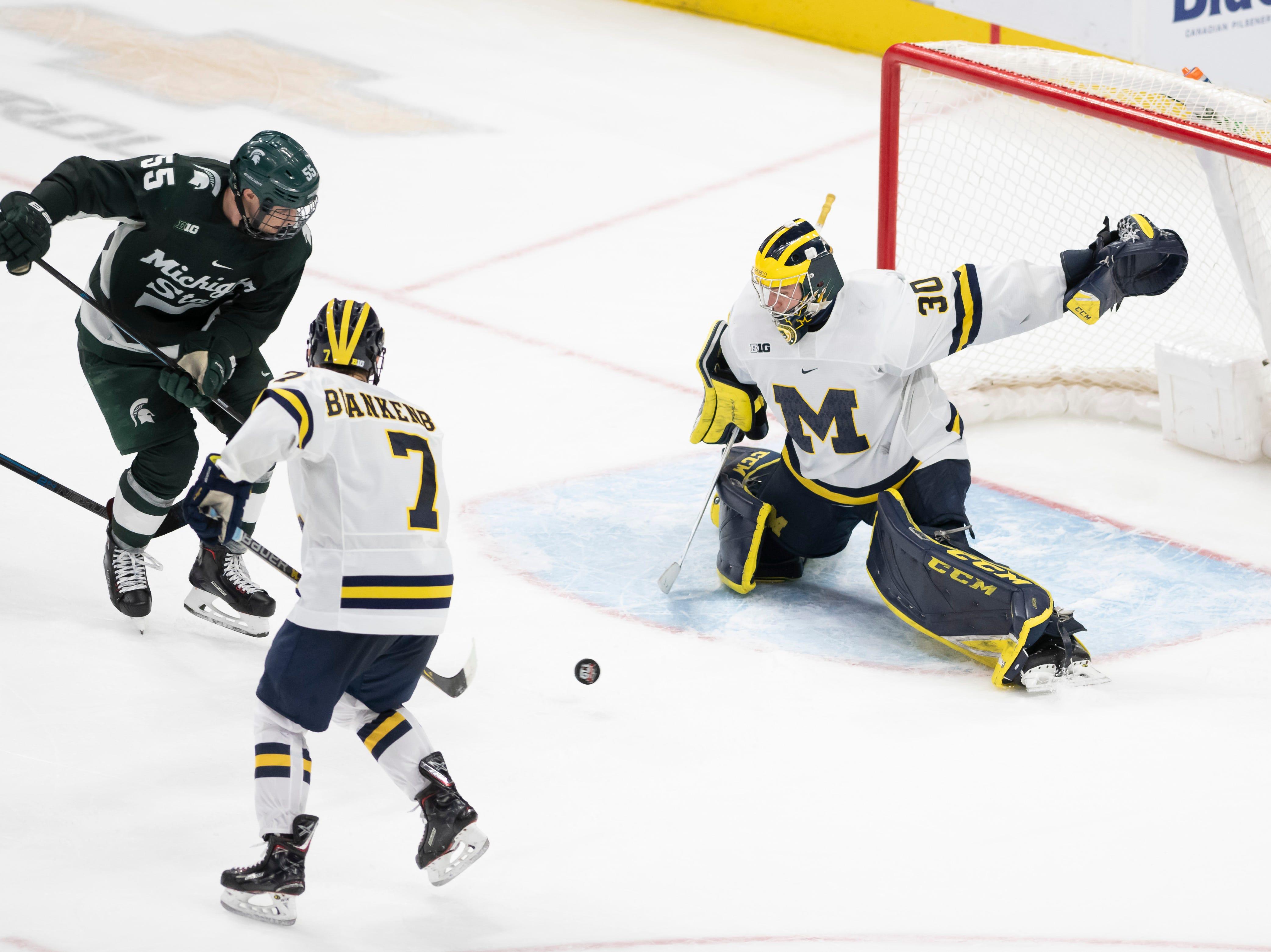 Michigan State forward Patrick Khodorenko can't get the puck past Michigan defenseman Nick Blankenburg and goaltender Hayden Lavigne in the third period.