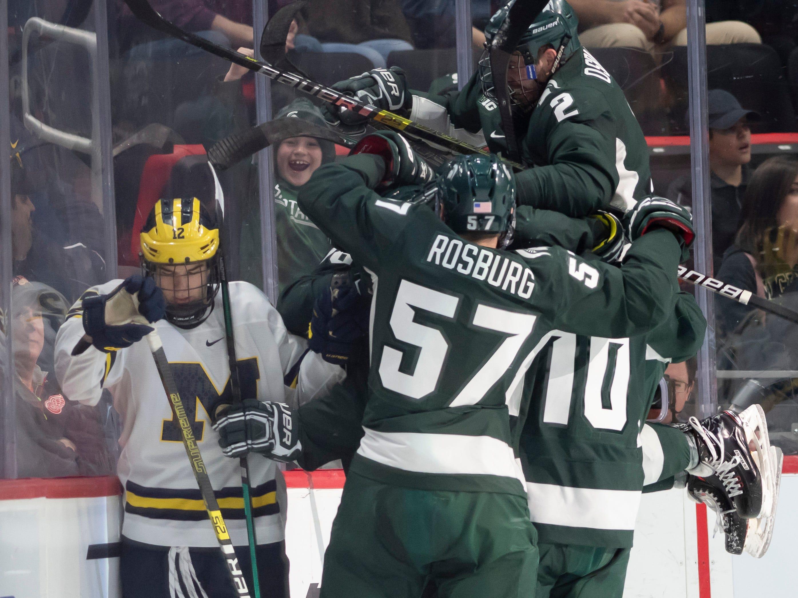 Michigan forward Dakota Raabe skates away as Michigan State celebrates a goal by Wojciech Stachowiak in the first period.
