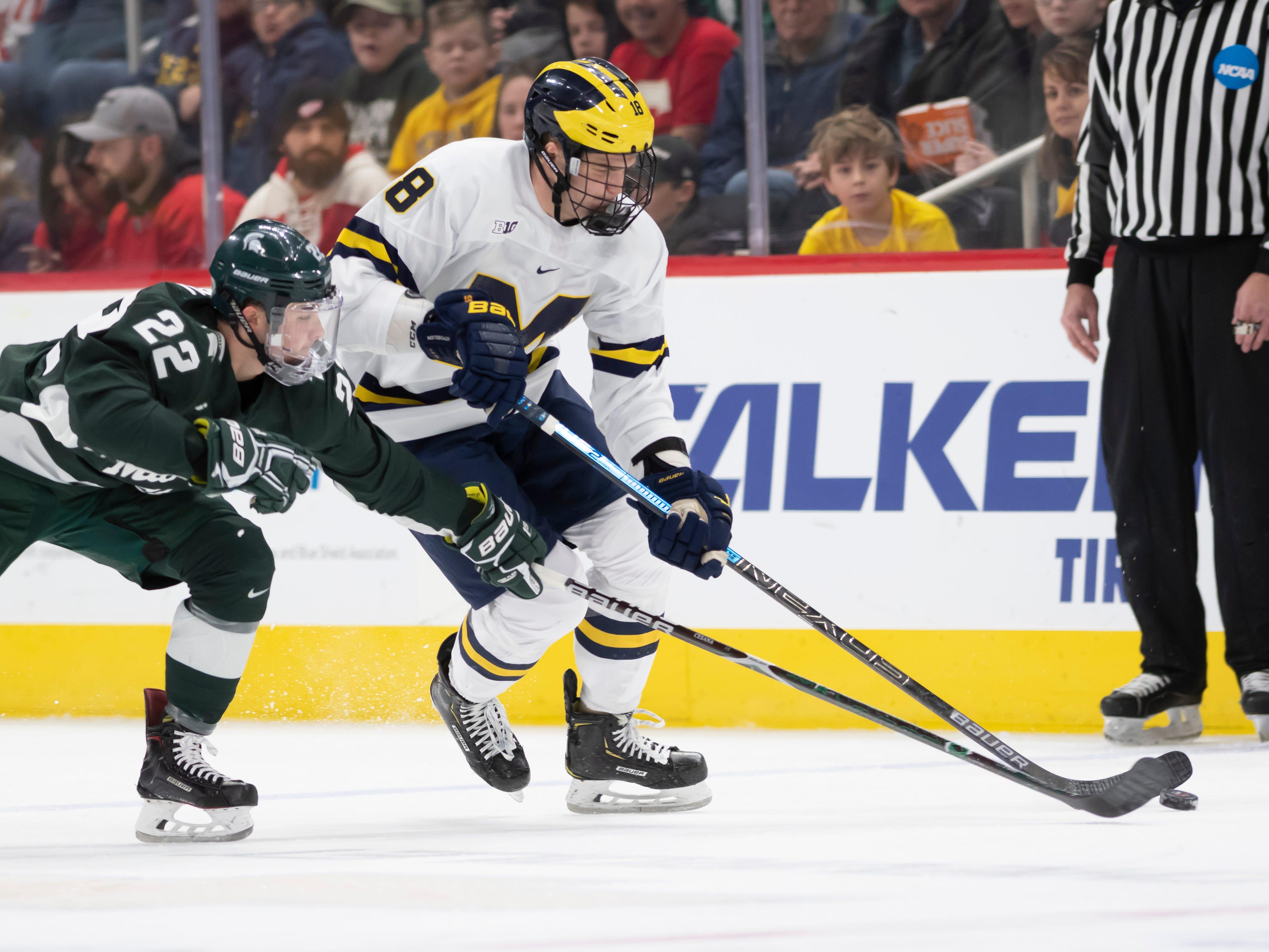Michigan State defenseman Dennis Cesana and Michigan forward Adam Winborg battle for the puck in the first period.