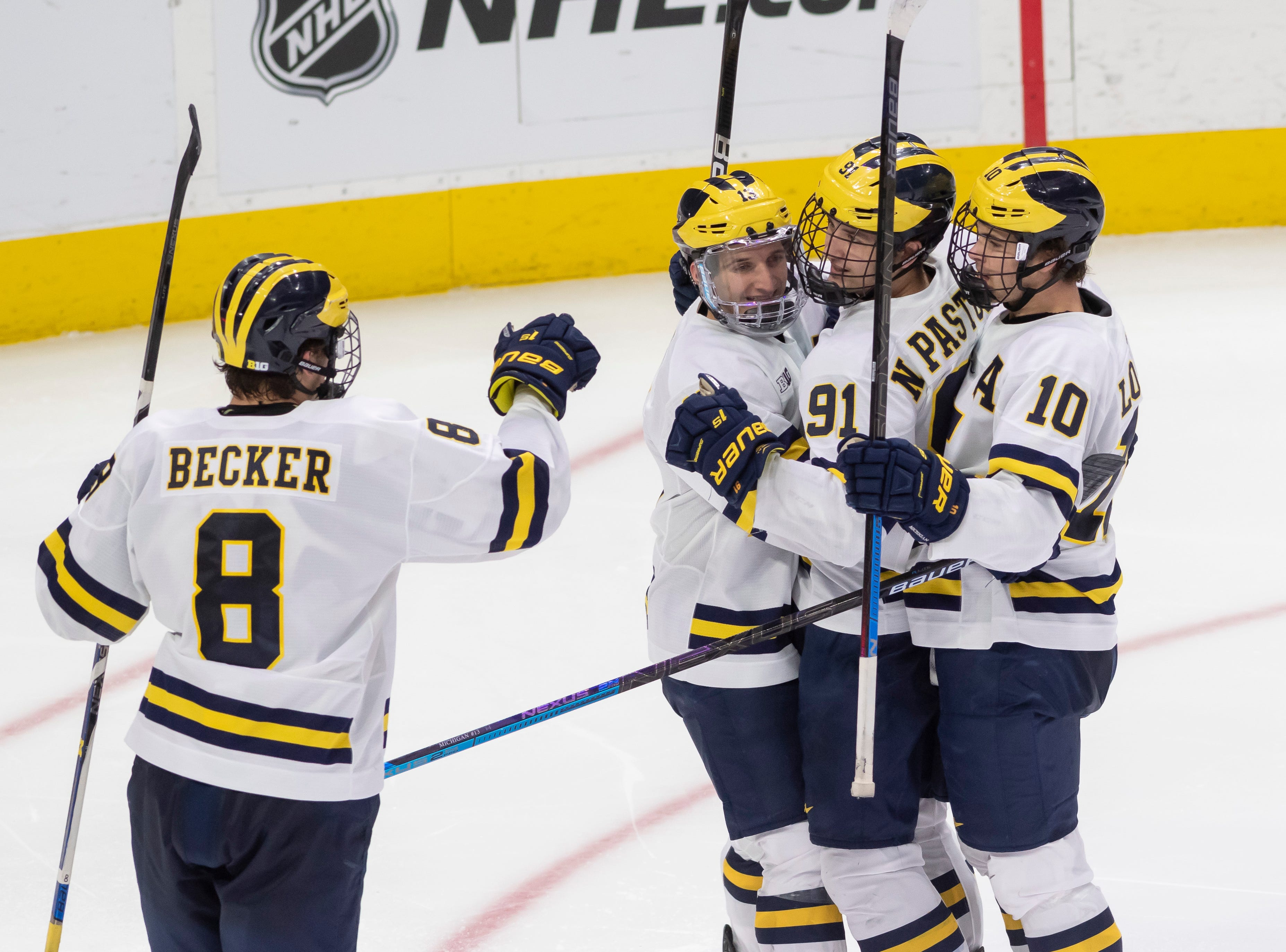 (From left) Michigan forward Jack Becker, forward Jake Slaker, forward Nick Pastujov, and forward Will Lockwood celebrate the tying goal by Pastujov in the third period.   The game ended in a tie.