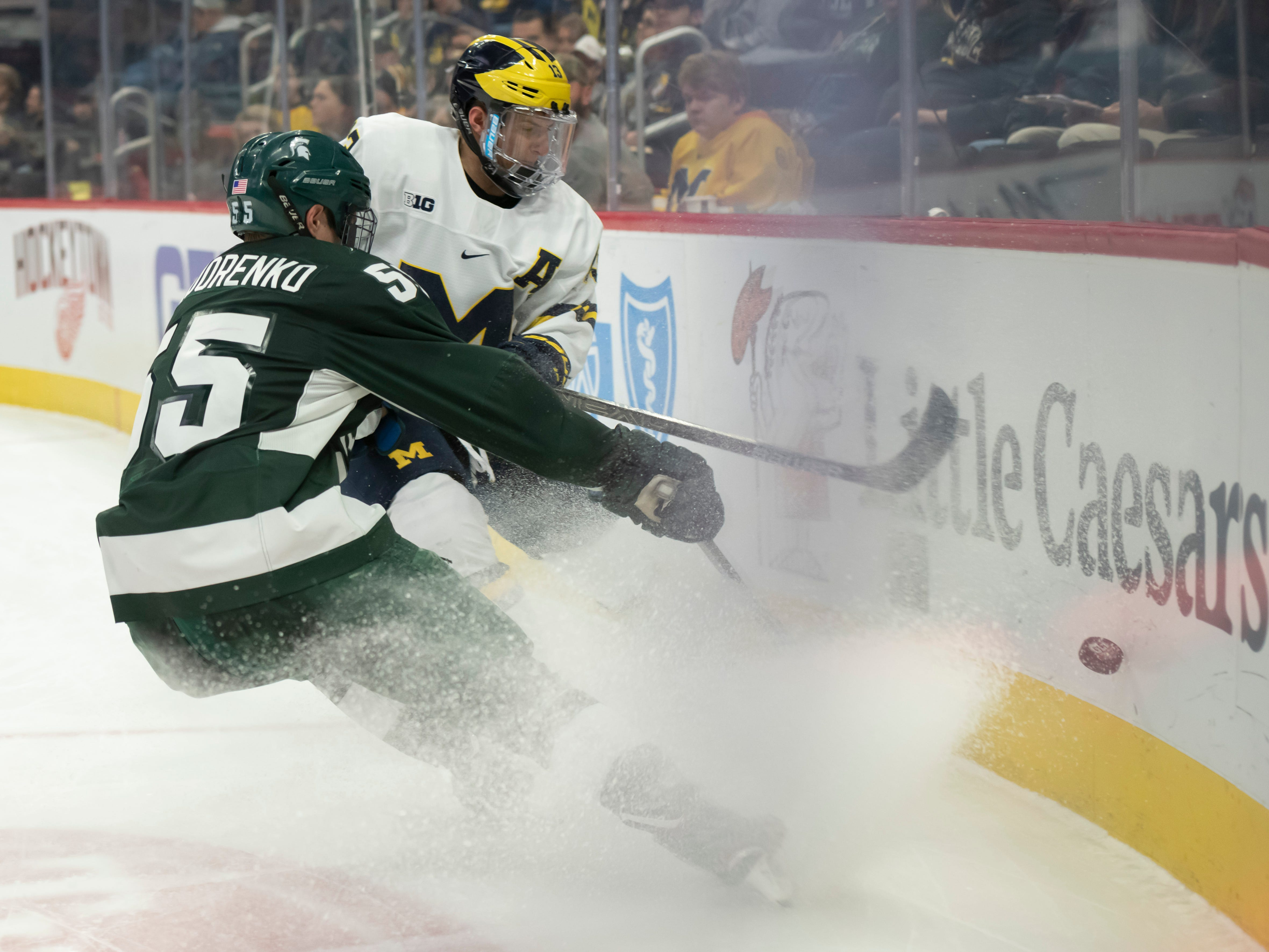 Michigan forward Jake Slaker and Michigan State forward Patrick Khodorenko battle for the puck in the first period.