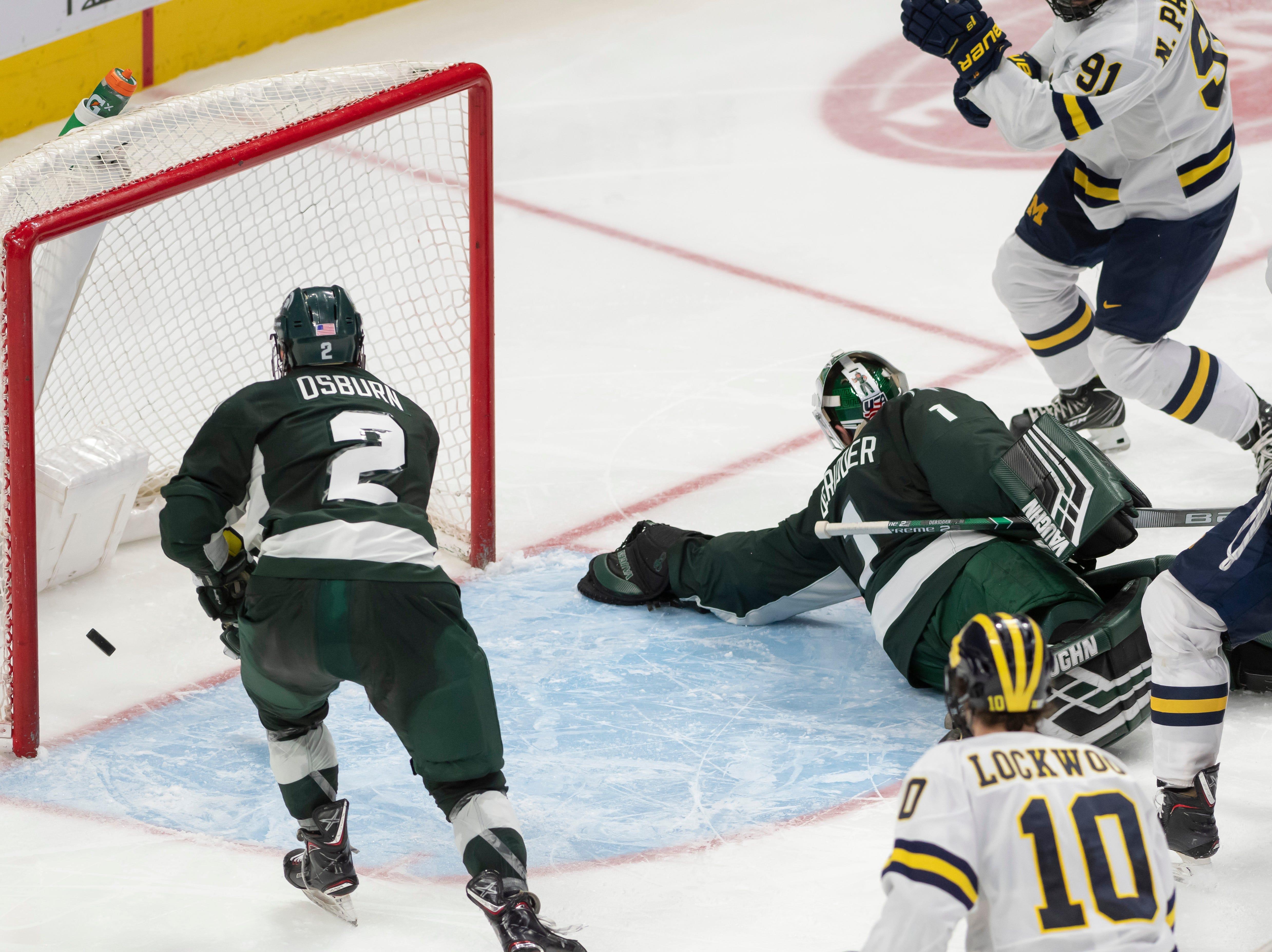 A goal by Michigan forward Nick Pastujov slips past Michigan State defenseman Zach Osburn and goaltender Drew DeRidder in the third period.