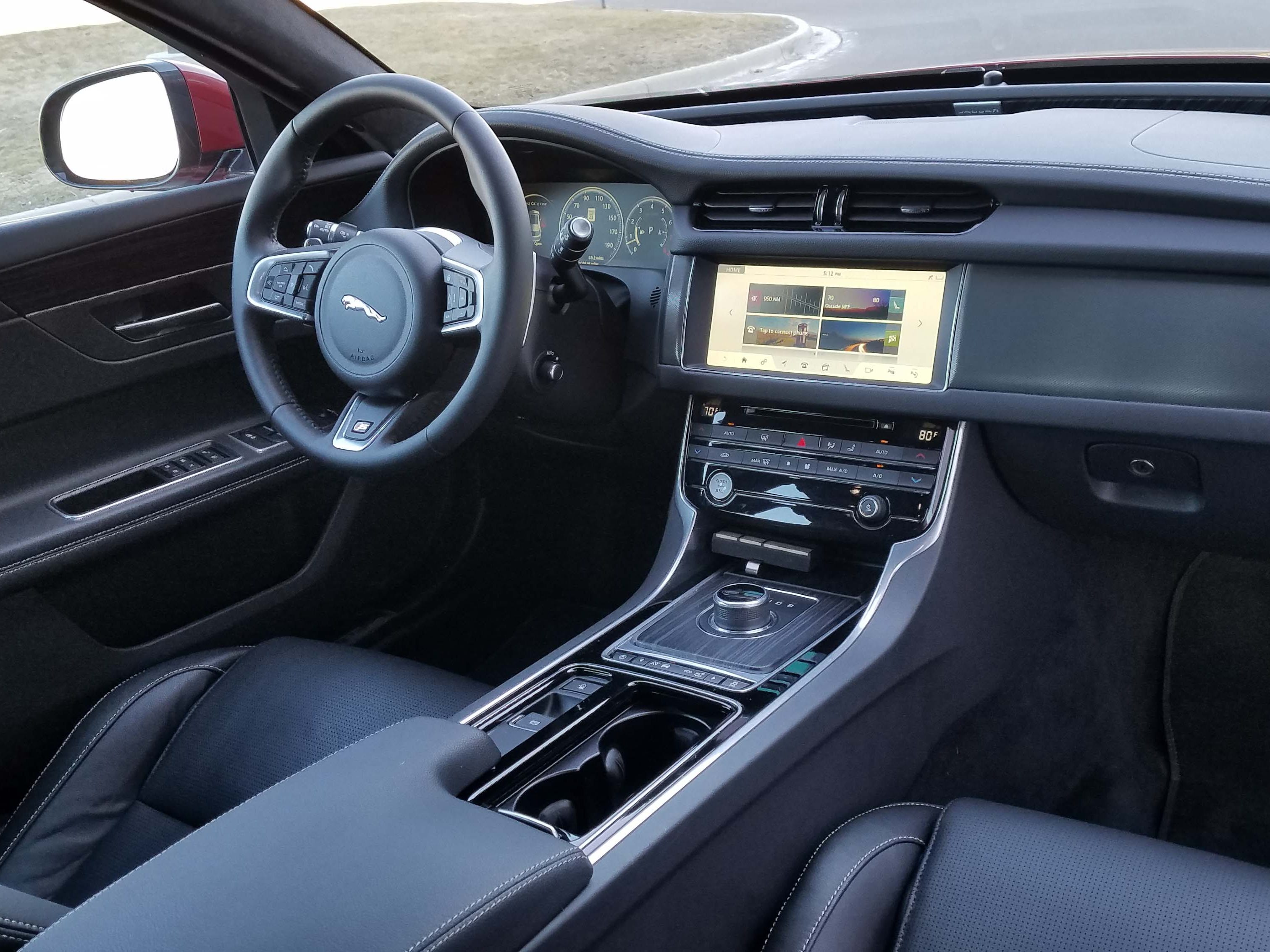 Compared to the Mercedes, the Jaguar XF Sportbrake's interior feels dated with a slow screen and plain layout. The pop-up, rotary shifter adds a touch of class.