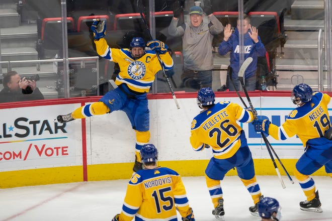 Lake Superior forward Diego Cuglietta leaps into the boards after scoring the game winning goal in overtime.             Lake Superior State wins 4-3 (OT) over Michigan State during the Great Lakes Invitational at Little Caesars Arena, in Detroit, Dec. 30, 2018.